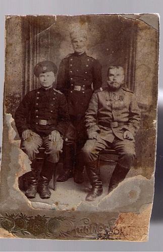 Помогите определить звание или хотя бы род войск человека стоящего в центре по фотографии